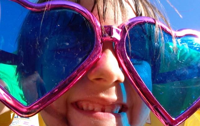 Una joven asistente al desfile, con unas gafas de corazones, para verlo mejor